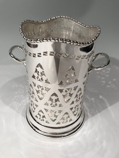 Antique silver plate wine bottle holder on a slightly splayed pedestal base rising to a cylindrical pierced body. The top is mounted with wavy beaded decoration